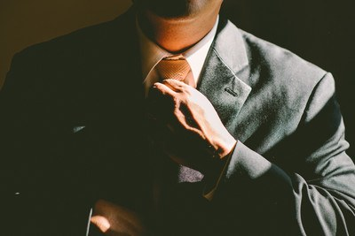 A Man in A Black Suit Loosening His Tie