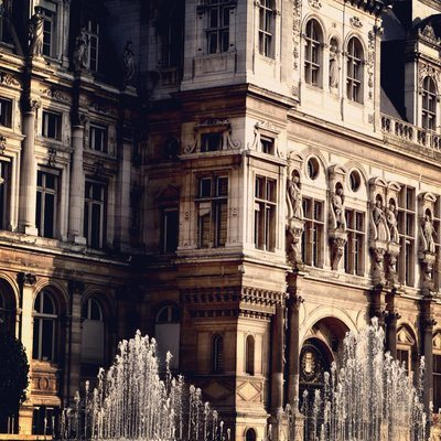A Sun-Kissed Baroque Building OverLooking Water Fountains