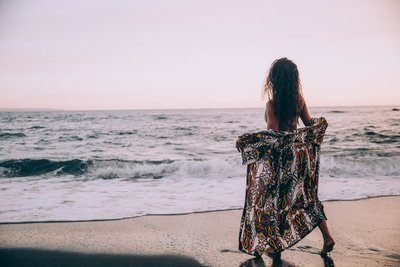 A Woman On A Beach Opens Her Sarong At The Rolling Waves