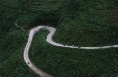 Aerial View of Curved Road Beside Mountains
