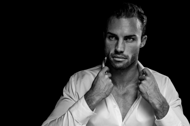Black & White Portrait of Man Wearing White Dress Shirt on Black Background