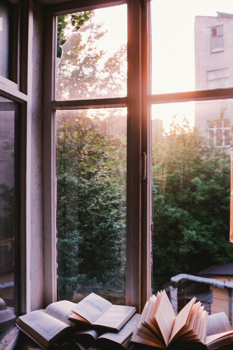 Books Beside Window at Sunset