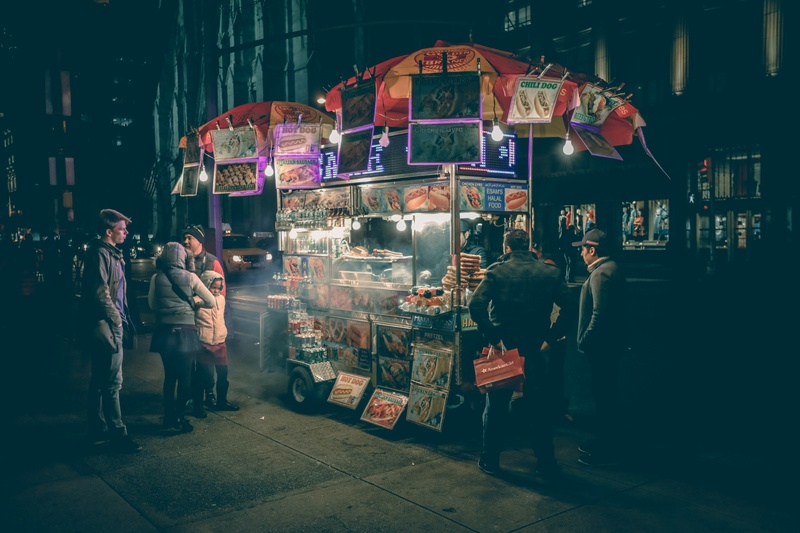 Group of People Standing Near Food Cart