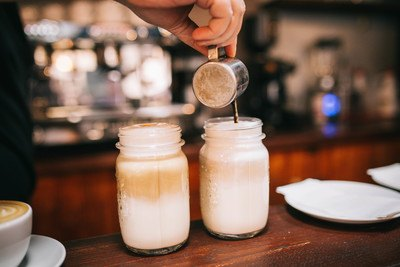 Hand Holding Stainless Steel Cup Pouring COffee on Glass Jars