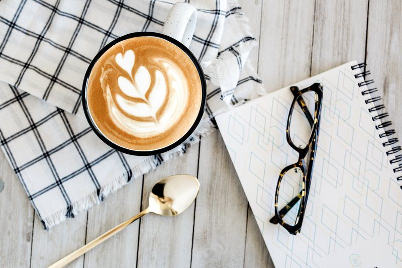 Latte Art On Rustic Table Next To Notebook And Glasses