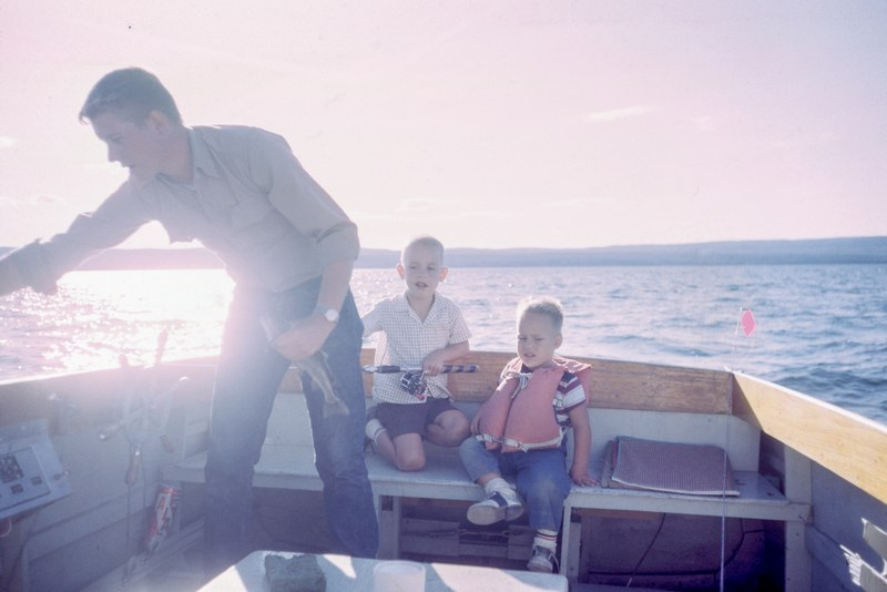 Man Holding Gray Fish Standing Beside Two Boys Sitting on Boat