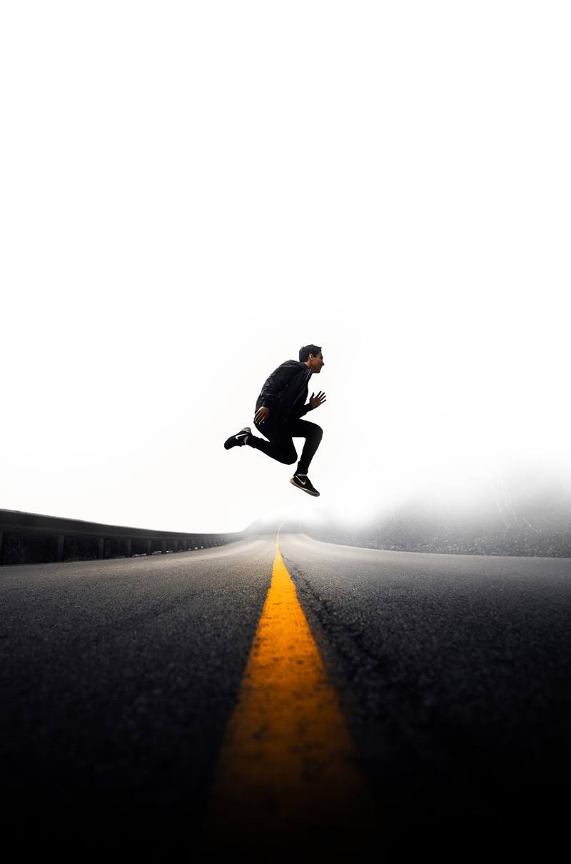 Man Jumping Above Gray And Yellow Concrete Road