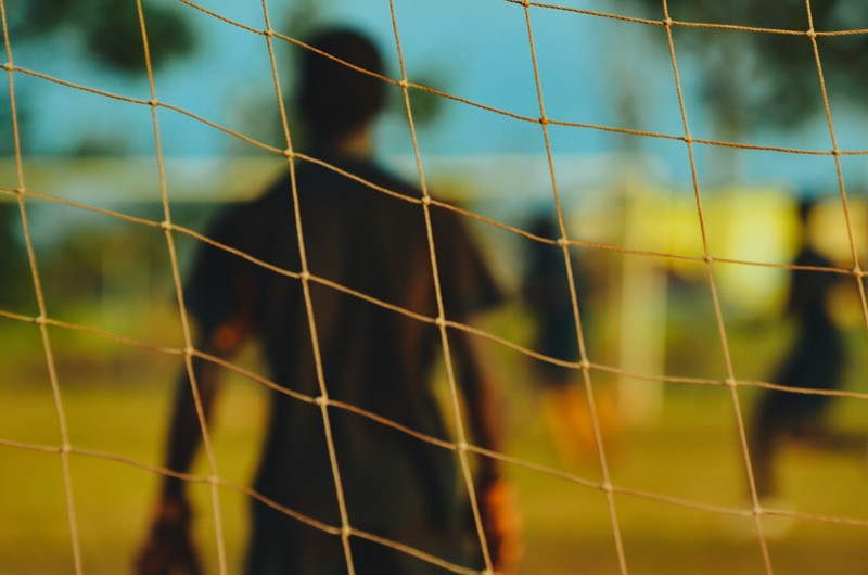 Man in Black T-Shirt Through Soccer Goal Post