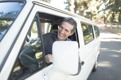 Man in Gray Sweater Leaning on Van Window
