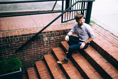 Men's Fashion Man In Shirt And Jeans Sat On Steps