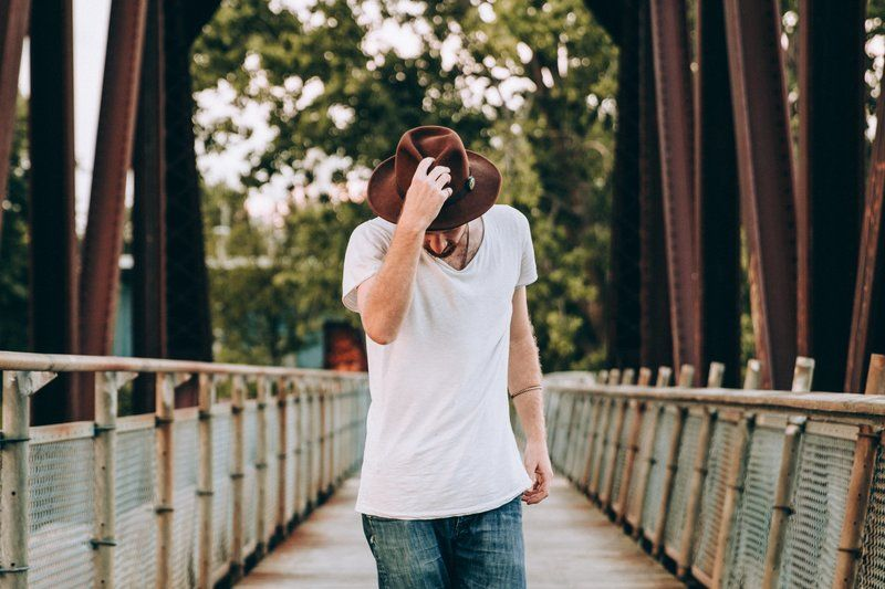 Men's Fashion Walking Across Bridge Holding Hat
