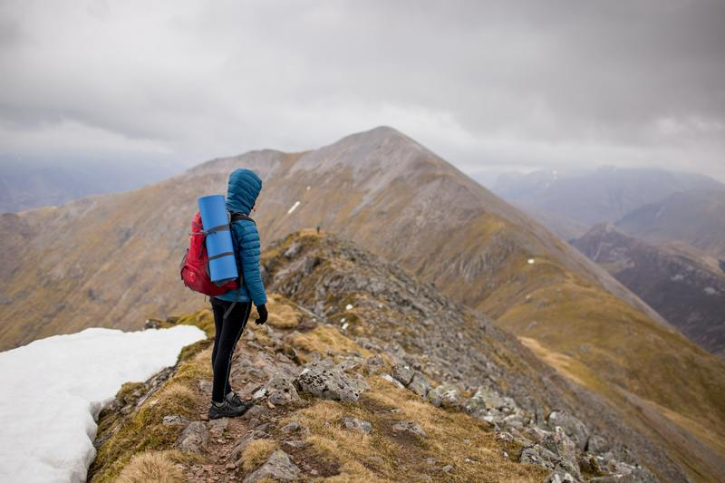 Person At Peak of Mountain Carrying Red Backpack