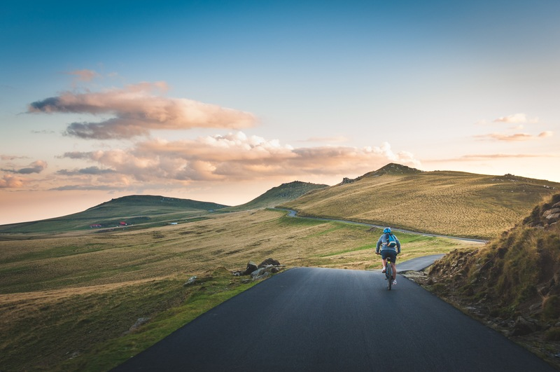 Person Cycling on Road Distance with Mountain