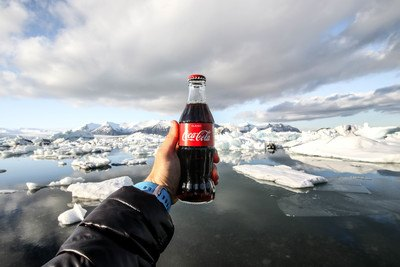Person Showing  Bottle of Coke in Front of Icebergs