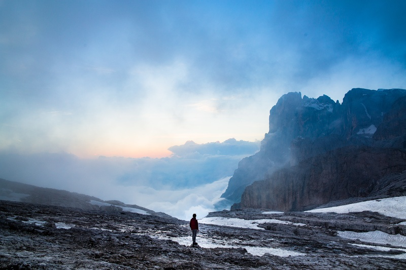 Person Standing Near the Cliff of the Mountain
