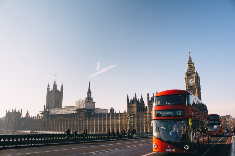 Red Double-Decker Bus Passing Palace of Westminster, London