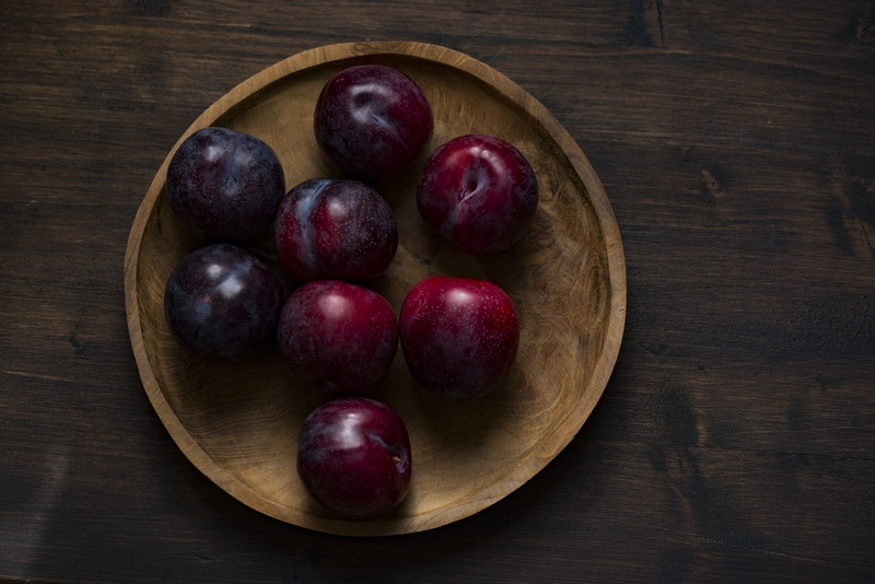 Red Plum Fruits on Round Brown Wooden Plate