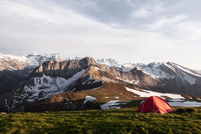 Red Tent on Grass Field Beside Ice Capped Mountain Nature