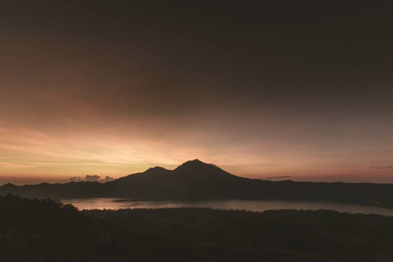 Silhouette of Mountain Near Water Under Brown Clouds
