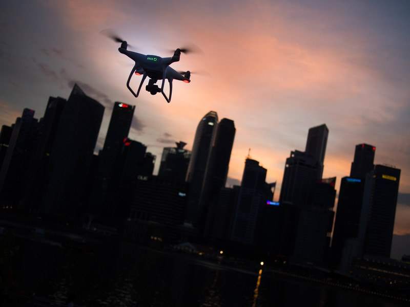 Silhouette of Quadcopter Drone Hovering Near the City