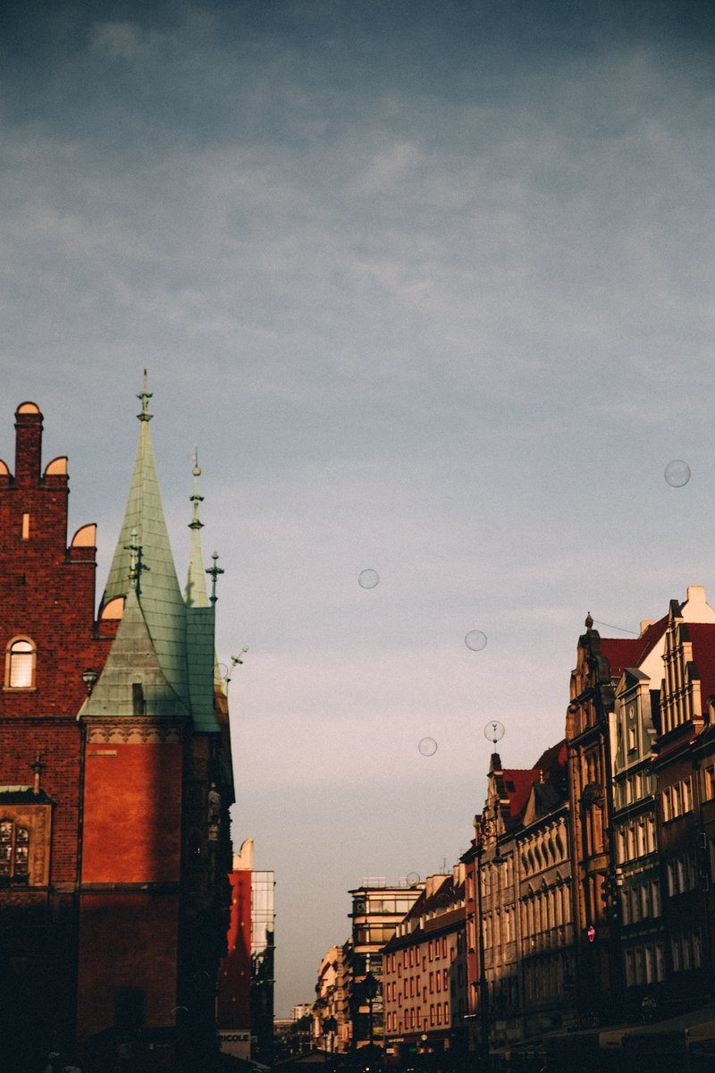 Soap Bubbles Float Over Red Brick Spires Of A Town
