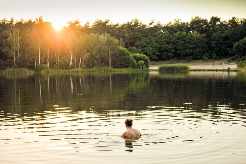 Topless Person in Lake Water Near Trees