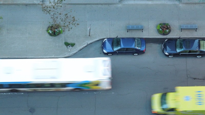 Two Blue Parked Vehicles Near Running Bus And Yellow-Green Truck Aerial