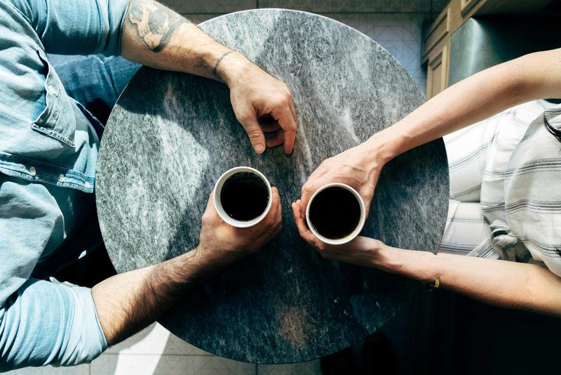 Two Man And Woman Holding Cups on Tables