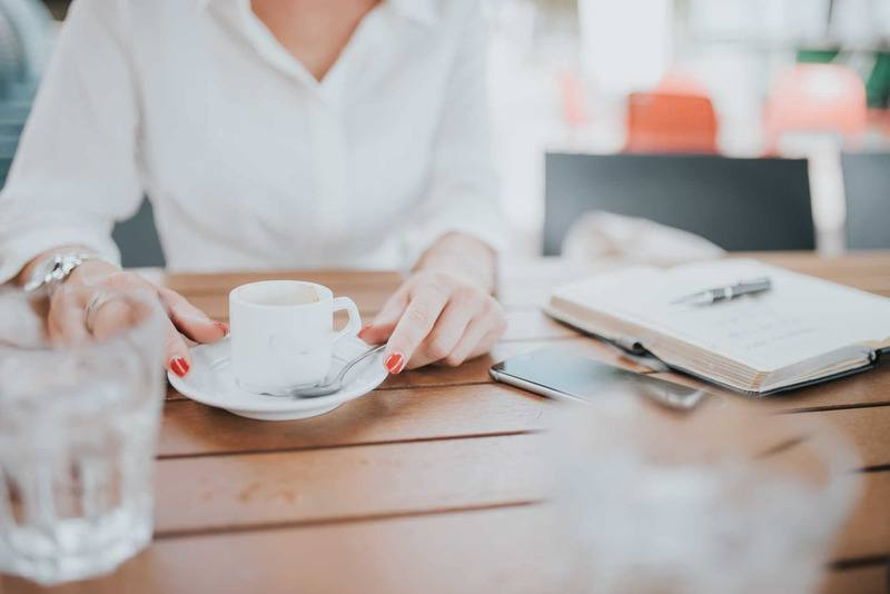 Woman Drinking Coffee with Notepad
