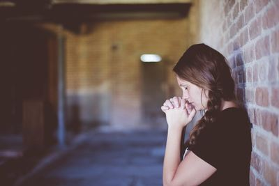 Woman Praying While Leaning Against Brick Wall