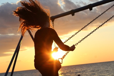 Woman Riding on Swing at Sunset