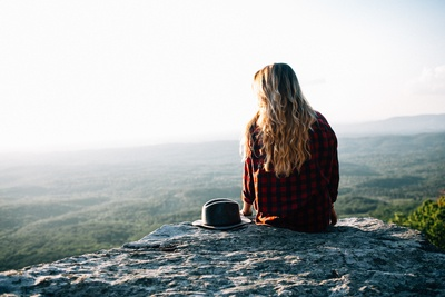 Woman Wearing Red And Black Gingham Shirt Sitting on Cliff with